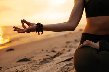 Meditating girl on the seashore during sunset. She is sitting in a lotus position. Close-up photo