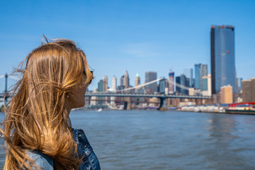 Wall Mural - Young lady standing on a ferry crossing Hudson river to Manhattan.