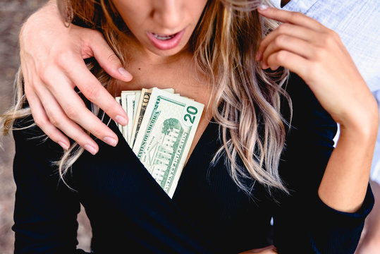 Midsection Of Man Harassing Woman With Paper Currency