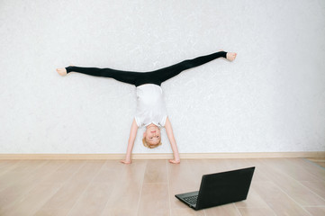 Schoolgirl watching online video on laptop and doing sports exercises - yoga, gymnastics, choreography. Stay at home. Concept of self isolation, quarantine, online education.