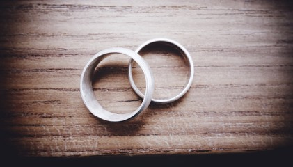 Close-up Of Two Wedding Ring On Table