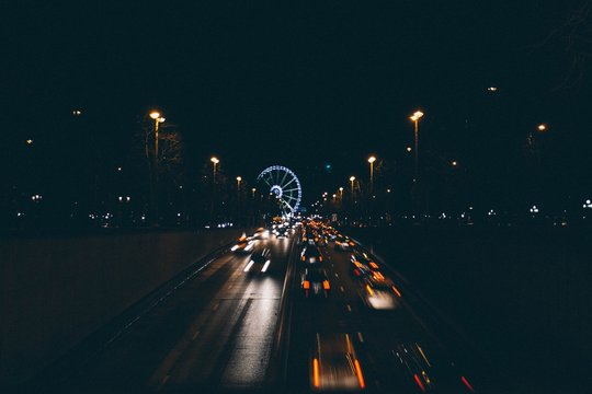 Traffic Moving On Road Leading To Ferris Wheel At Night