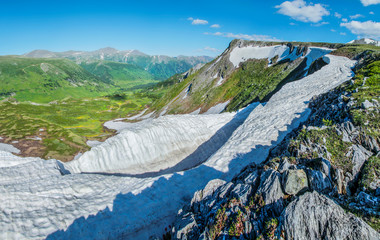 Wall Mural - View from the top, mountain landscape. Snow, glaciers and spring greens. Altai, Russia.