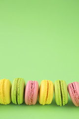 Acrylic Prints Macarons Row of colorful macarons on green