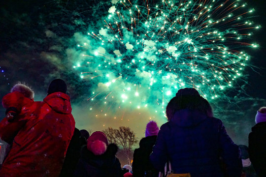 many people in warm winter clothes look at the green fireworks in the night sky, holiday, new year, view from the back