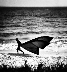 Tilt Shit Image Of Man Running On Shore With Kite At Beach Against Sea