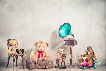 Antique gramophone phonograph, and retro Teddy Bear toys on chair, old luggage, wooden horse, plane front concrete wall background. Listening to nostalgic music concept. Vintage style filtered photo