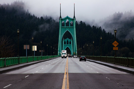 Vehicles On St Johns Bridge Against Tree During Foggy Weather