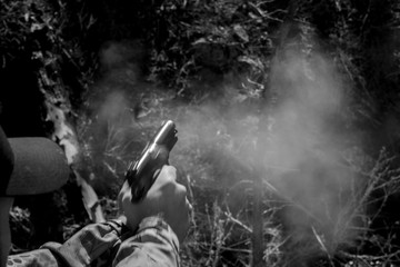 Cropped Image Of Man Shooting Against Trees