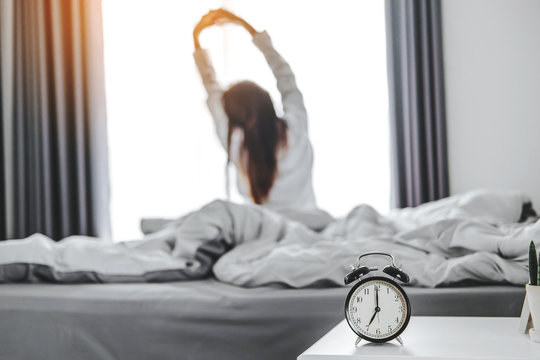 Asian woman wake up on bed stretching feeling happy and fresh enjoying in the morning