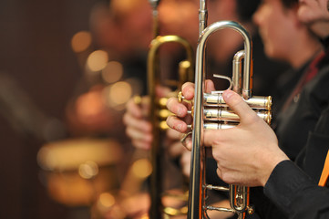 trumpet held by trumpeter waiting his turn, with other trumpets out of focus behind