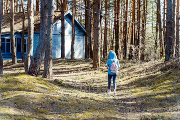 A lonely figure of a young woman hiking into the woods alone. A small cottage on the background.