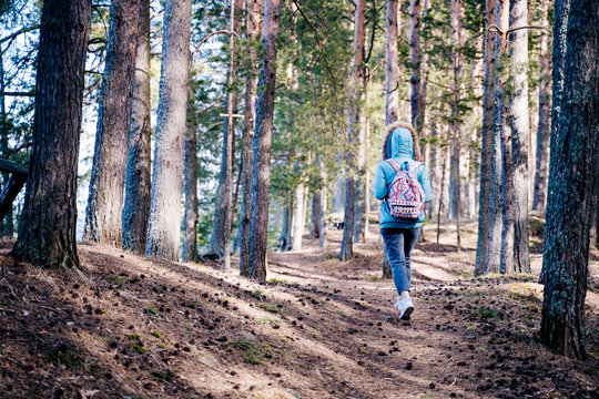 A lonely figure of a young woman hiking into the woods alone. The concept of being lonely and finding your own way.