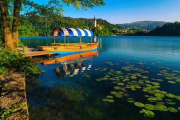 Fototapete - Wooden Pletna boat moored at the pier, lake Bled, Slovenia