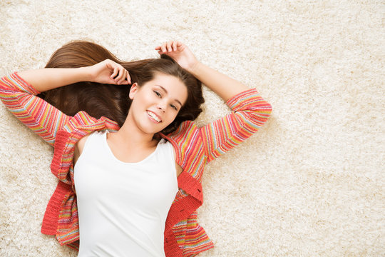 Woman Lying Down on White Carpet Floor, Casual Happy Girl on Floor Top View