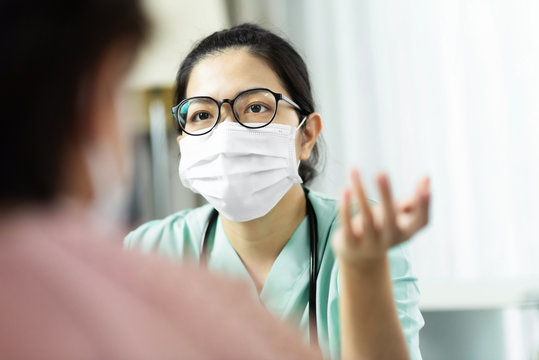 Asian woman Doctor in green uniform wear eyeglasses and surgical mask talking, consulting and giving advice to Elderly female patient at the hospital.