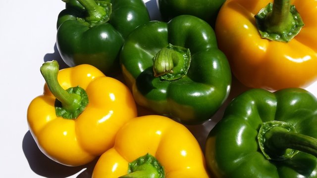 High Angle View Of Yellow And Green Bell Peppers On Sunny Day