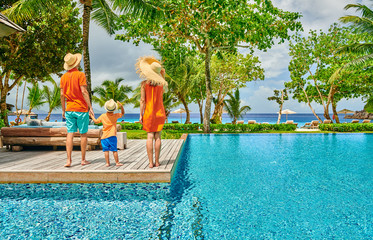 Wall Mural - Family of three by poolside. Resort swimming pool at Seychelles.