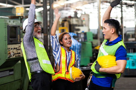 Man and Woman engineering wearing safety goggles and hard hats giving high five and celebrating success. Metal lathe industrial manufacturing factory