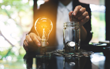 Businesswoman holding a light bulb over coins stack on the table while putting coin into a glass jar for saving energy and money concept