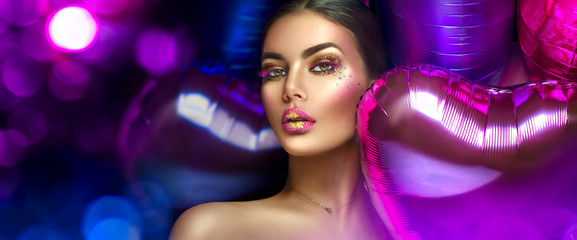 Spoed Fotobehang Beauty Beauty fashion model girl creative art makeup, over purple, pink and violet air balloons background. Woman face Make-up with gems, pink with gold lips, purple eyeshadows. Widescreen.