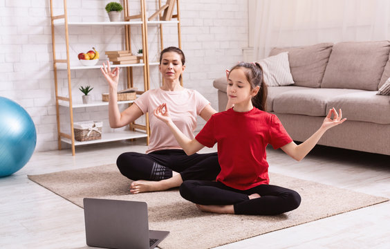 Home sports. Mother and daughter doing yoga or meditation while watching online tutorial on laptop