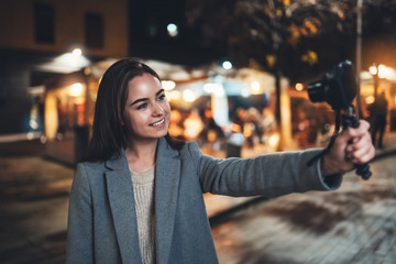 Fotomurales - Female vlogger recording with digital camera. Smiling woman taking selfie video on light night city. Traveler making picture for her videoblog. Vlogger uses photo camera for shoot social media