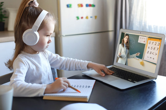 Smart small preschooler girl in headphones watch online lesson and communicate with teacher at home, little child in earphones study on Internet using laptop wireless connection.