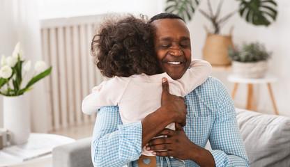 Grandparent grandchild relationship. Senior African American man hugging his granddaughter at home