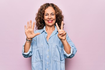 Wall Mural - Middle age beautiful woman wearing casual denim shirt standing over pink background showing and pointing up with fingers number seven while smiling confident and happy.