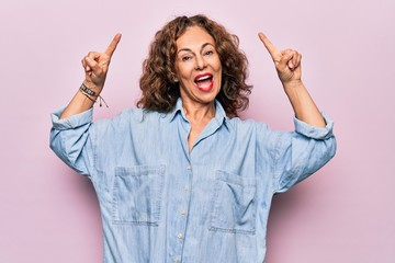 Wall Mural - Middle age beautiful woman wearing casual denim shirt standing over pink background smiling amazed and surprised and pointing up with fingers and raised arms.