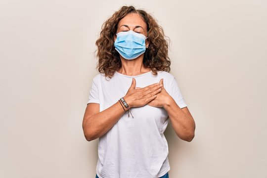 Middle age woman wearing coronavirus protection mask for covid-19 epidemic virus smiling with hands on chest, eyes closed with grateful gesture on face. Health concept.