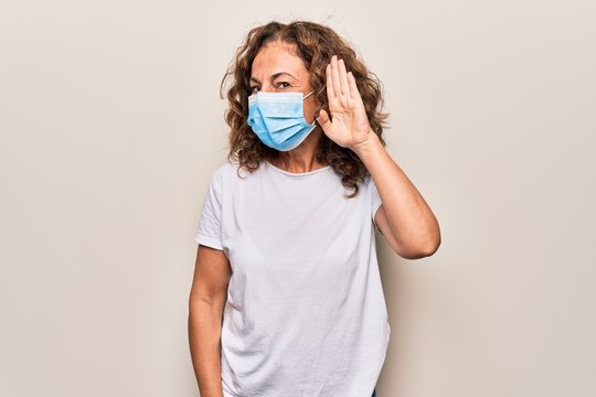 Middle age woman wearing coronavirus protection mask for covid-19 epidemic virus smiling with hand over ear listening and hearing to rumor or gossip. Deafness concept.