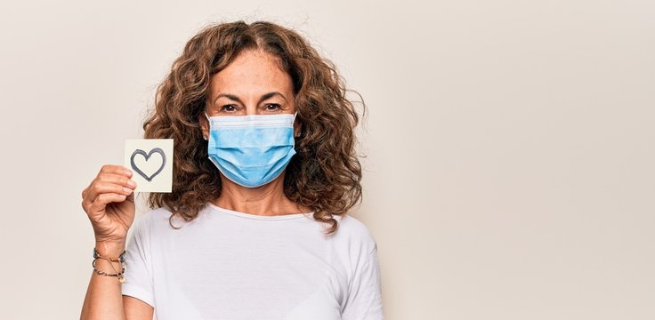 Middle age woman wearing coronavirus protection mask and holding love reminder on paper note looking positive and happy standing and smiling with a confident smile showing teeth
