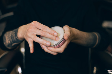 balm-wax. beard oils. barber shop beard care.jar with wax in the hands of a barbershop