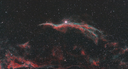 Veil nebula also known as NGC 6960 in Cygnus constellation, taken in the dark space with stars at background.