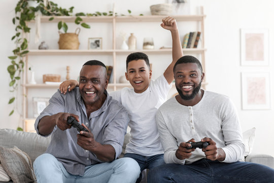 Cheerful Black Boy Playing Videogames With Father And Grandfather At Home