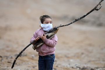 Alejandra holds branches as she goes for a walk along the beach with her father after the restrictions for children were partially lifted for the first time in six weeks, during the outbreak of coronavirus disease (COVID-19) in Gijon