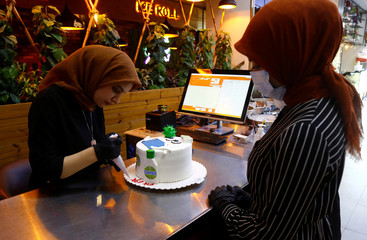 A woman writes the name of a girl on a birthday cake with figures of Dettol bottles and models of the coronavirus, during the outbreak of the coronavirus disease (COVID-19), at a cake shop in the holy city of Najaf