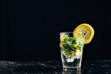glass of mojito decorated with a lemon on a dark background. close horizontal picture