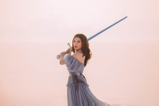 Art Portrait young beautiful brave warrior woman princess. Medieval queen holds steel silver magic sword. Concept Protection freedom. long hair retro vintage gray blue dress. White winter snow nature