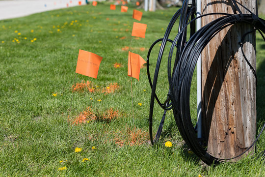 Fiber optic cable, orange marking flags and utility pole. Concept of digging safety, utility locate service and high speed internet