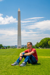 Wall Mural - Young guy exploring Washington city near Washington monument on sunny day with blue sky background.