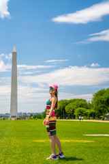 Fototapete - Young sexy girl in a dress exploring Washington city near Washington monument on sunny day