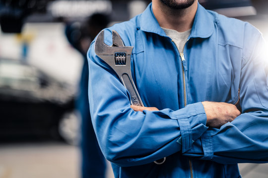 No face shot of car mechanic male worker holding equipment tool standing in maintenance and repair automotive garage shop. Another man checking vehicle condition on car lift behind in workshop.
