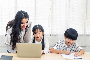 Asian parent teaching homework to children after learning online education class from school teacher at home. Mother explaining knowledge in computer laptop to daughter and helping son lecture notes.