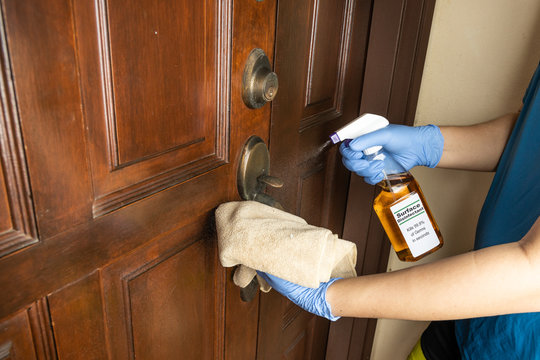 Person disinfecting door knob with disinfectant spray to kill germs, bacteria, virus.