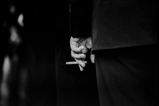 Zigarette mit Hand und schwarzem Hintergrund in Schwarzweiss