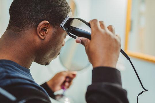 Personal hygiene, african american man cutting his own hair in the bathroom