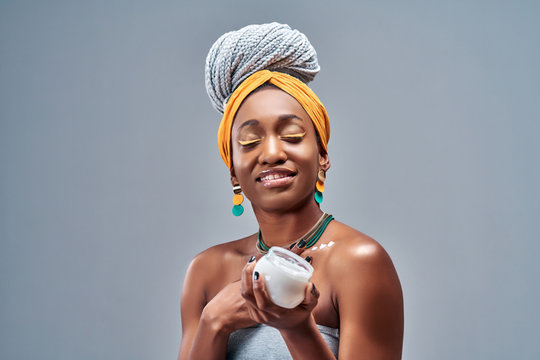 Beautiful young African American woman applying cream on skin on grey background